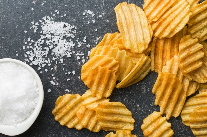 salty potato chips on dark background