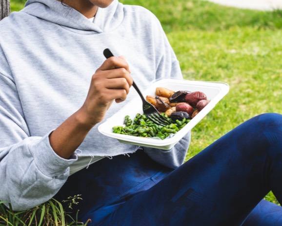 Eating healthy prepared meal outside